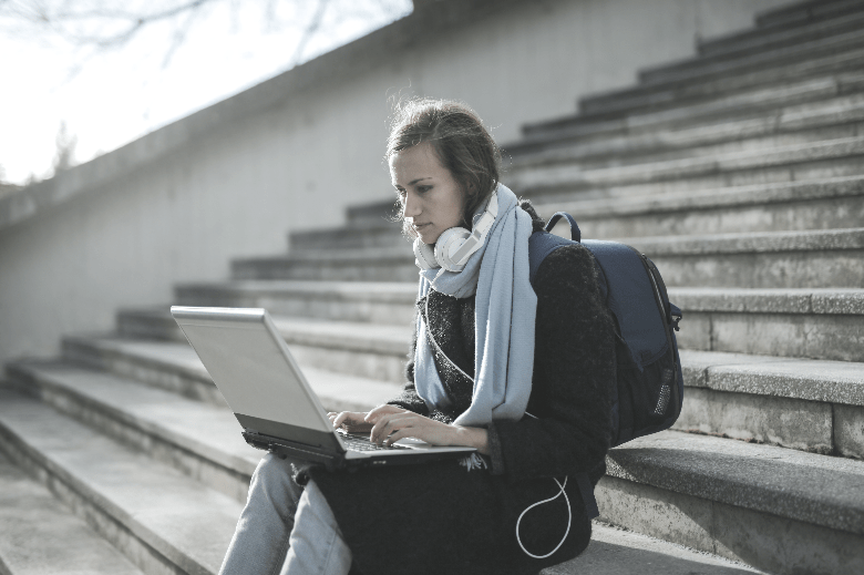 Student on law school steps with laptop.