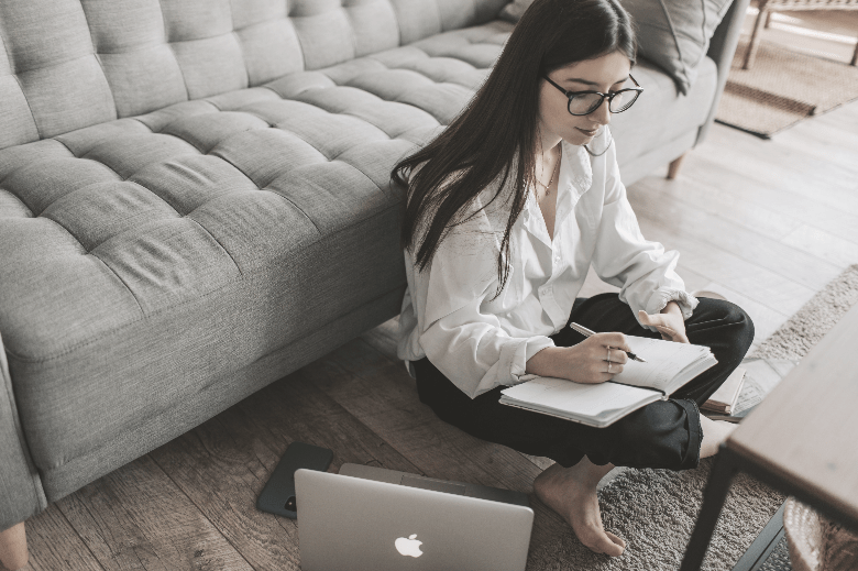 Young woman studying for the LSAT on the floor with a notebook and laptop.