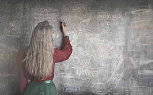 Young Woman Solving Data Sufficiency Problem at Chalkboard